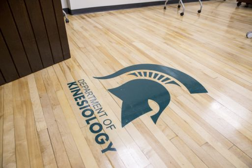 Floor sign of the Spartan helmet with the words Department of Kinesiology